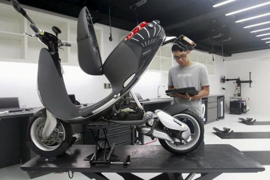 A mechanic examines a Gogoro Smartscooter which is connected to a tablet, in its shop in Taipei.