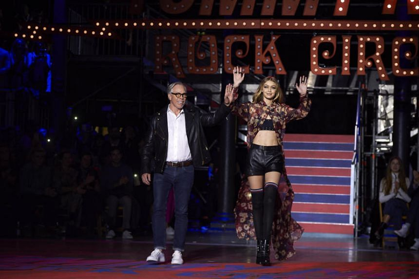 US designer Tommy Hilfiger (left) and US model Gigi Hadid greet the crowd after the catwalk show for the Spring/Summer 2018 collection on the fifth and final day of The London Fashion Week Women's in London.