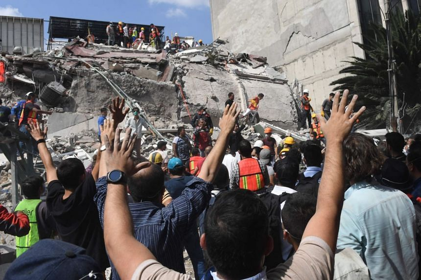 Rescuers look for survivors amid the rubble of a collapsed building after a powerful quake in Mexico City on Sept 19, 2017.
