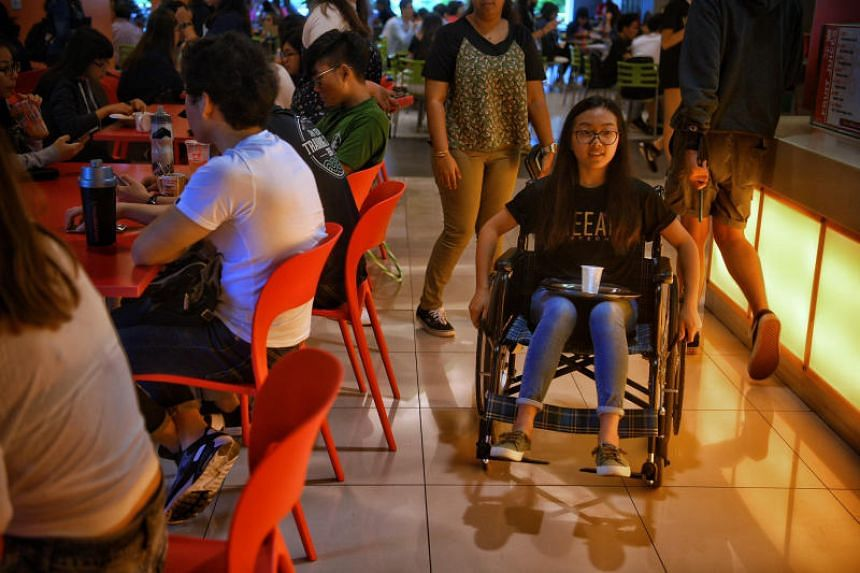 A Ngee Ann Polytechnic student balances a tray of water as she tries navigating around in a wheelchair at the canteen.