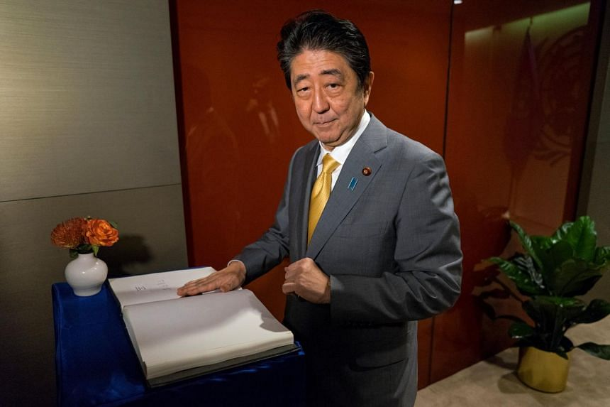 Japanese Prime Minister Shinzo Abe signs a guest book before a meeting with United Nations Secretary-General Antonio Guterres.