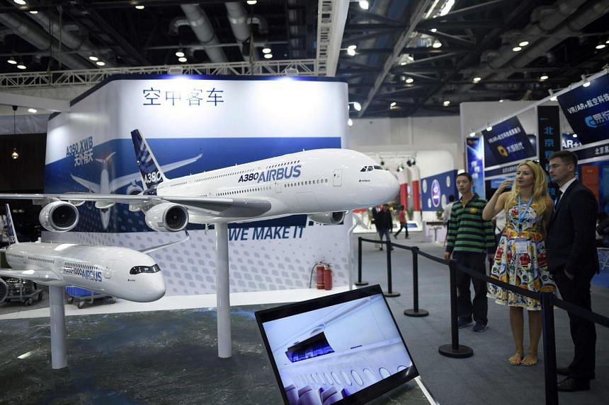 Visitors look at an Airbus A380 and an Airbus A350 plane model at the Beijing International Aviation Expo in Beijing, on Sept 19, 2017.