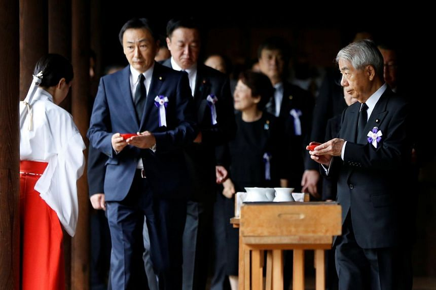 A group of lawmakers including Japan's ruling Liberal Democratic Party (LDP) lawmaker Hidehisa Otsuji (right) sip sake as a ritual after offering prayers for the war dead at the Yasukuni Shrine in Tokyo, Japan, on Aug 15, 2017.