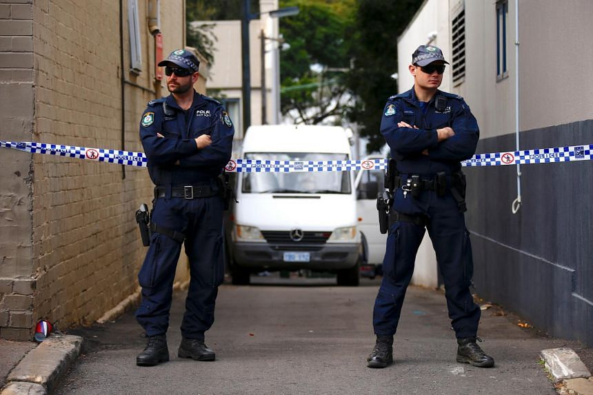 Police officers block a small alley where police vans are parked at a home being searched after Australian counter-terrorism police arrested four people in raids across several Sydney suburbs in Australia, on July 30, 2017.