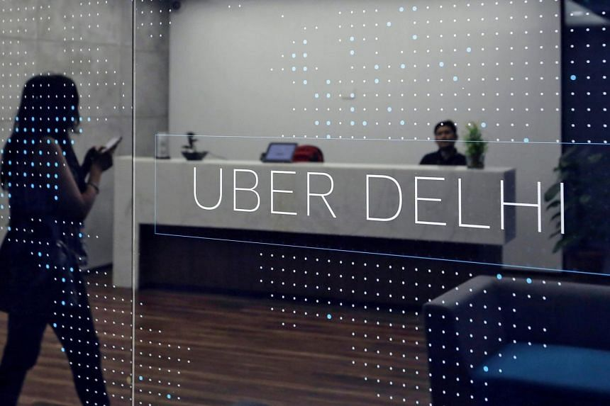 An employee walks inside the office of ride-hailing service Uber in Gurugram,  New Delhi, on April 19, 2016.