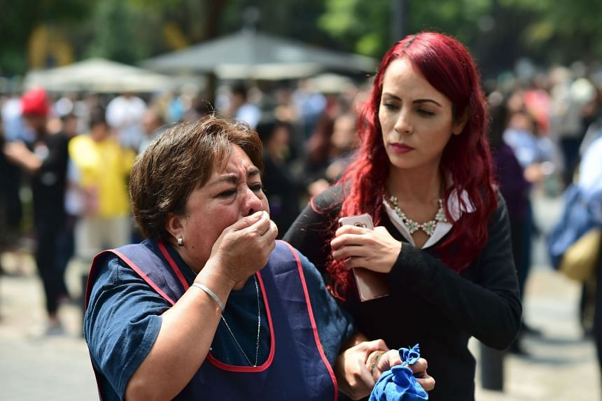 A woman reacts as an earthquake rattles Mexico City.