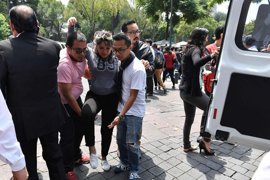 A woman is assisted after a real quake rattled Mexico City while an earthquake drill was being held in the capital.