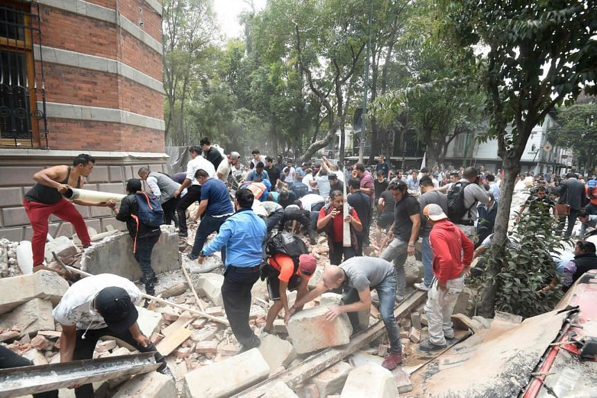 People remove debris of a damaged building after an earthquake rattled Mexico City.