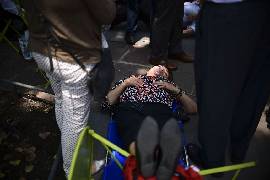 A woman is assisted after an earthquake rattled Mexico City.