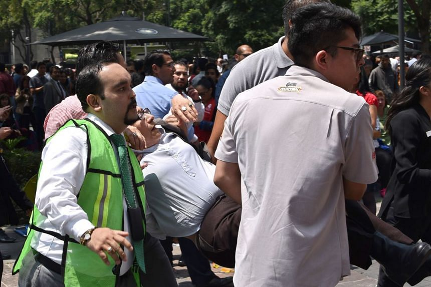 A woman is assisted after a quake rattled Mexico City.