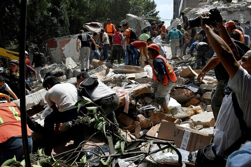 People remove debris of a building which collapsed after a quake rattled Mexico City.