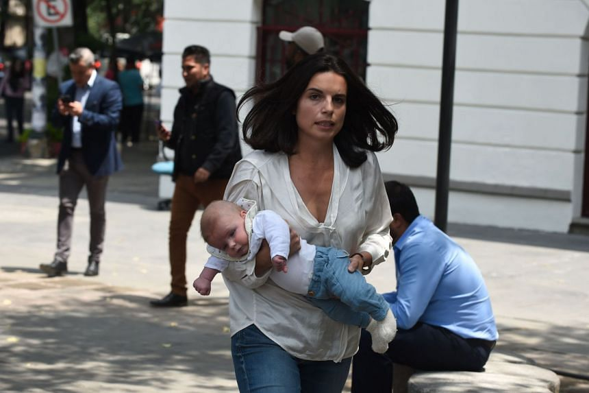 A woman rushes with her baby along the streets after a quake rattled Mexico City.
