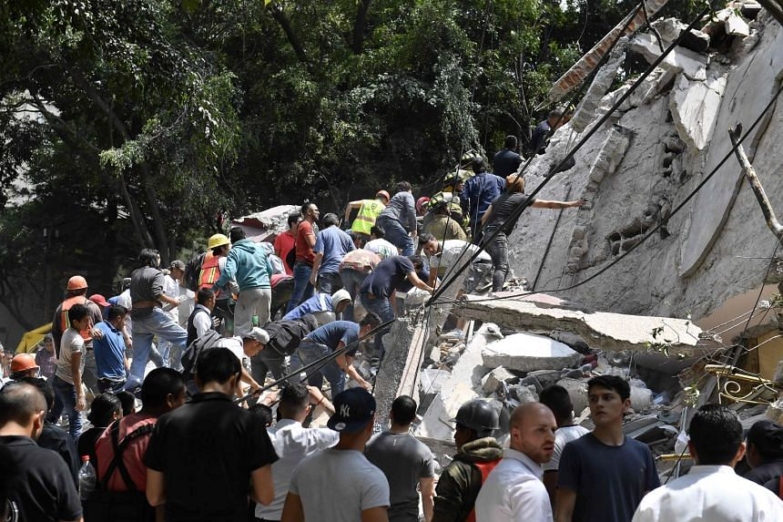 People remove debris of a collapsed building looking for possible victims.