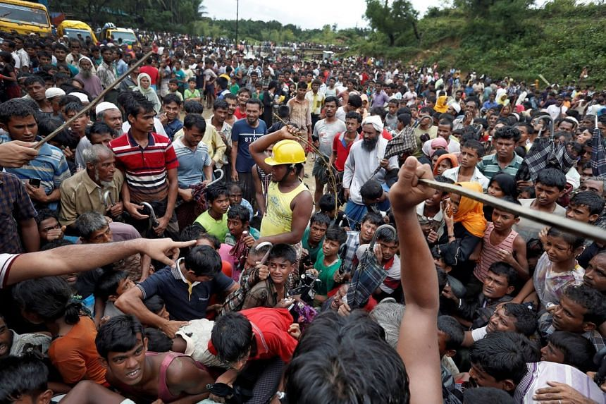 Refugees gathering to receive aid at a camp in Cox's Bazar, Bangladesh, yesterday. South-eastern Bangladesh now hosts some 700,000 Rohingya, in addition to those who fled earlier.