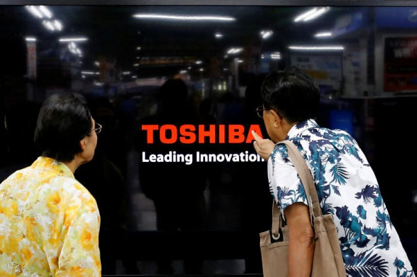 Shoppers look at Toshiba Corp's Regza television at an electronics store in Yokohama, south of Tokyo. PHOTO: REUTERS