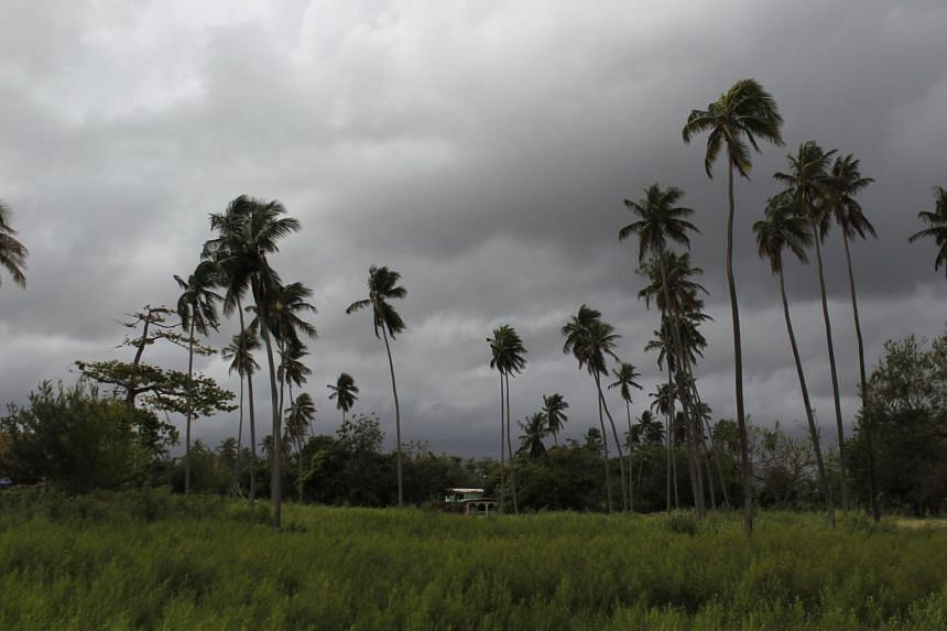 A house sits surrounded by palm trees as Hurricane Maria approaches the island in Loiza, Puerto Rico on Sept 18, 2017.