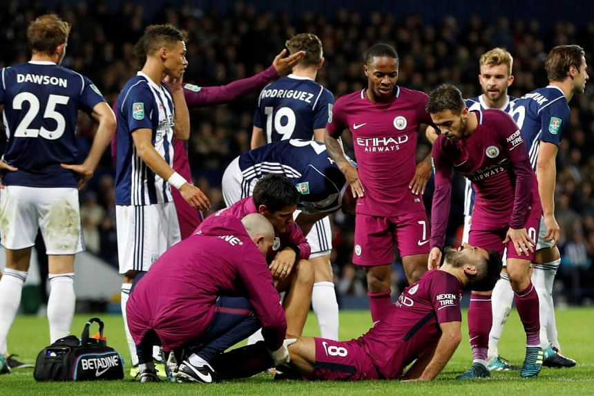 Manchester City's Ilkay Gundogan receives medical attention after sustaining an injury on Sept 20, 2017.