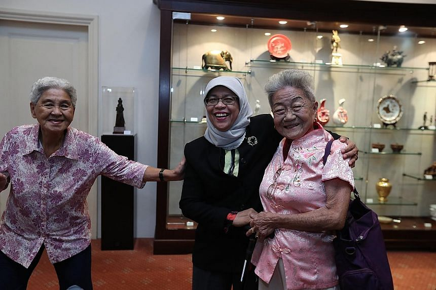 Madam Sim Goon Hua (left) and Madam Lim Ah Kheoh posing for a picture with President Halimah Yacob yesterday at the Istana. During lunch of steamed fish, chicken, vegetables and rice, they chatted in Mandarin and Malay with the President about their