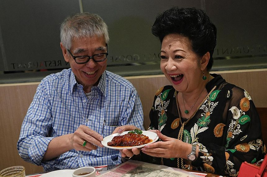 Robert Chua presenting actress Nancy Sit with the Kam's Roast special Iberico Char Siu to commemorate their 50 years of friendship at the restaurant in Singapore, which he brought in.