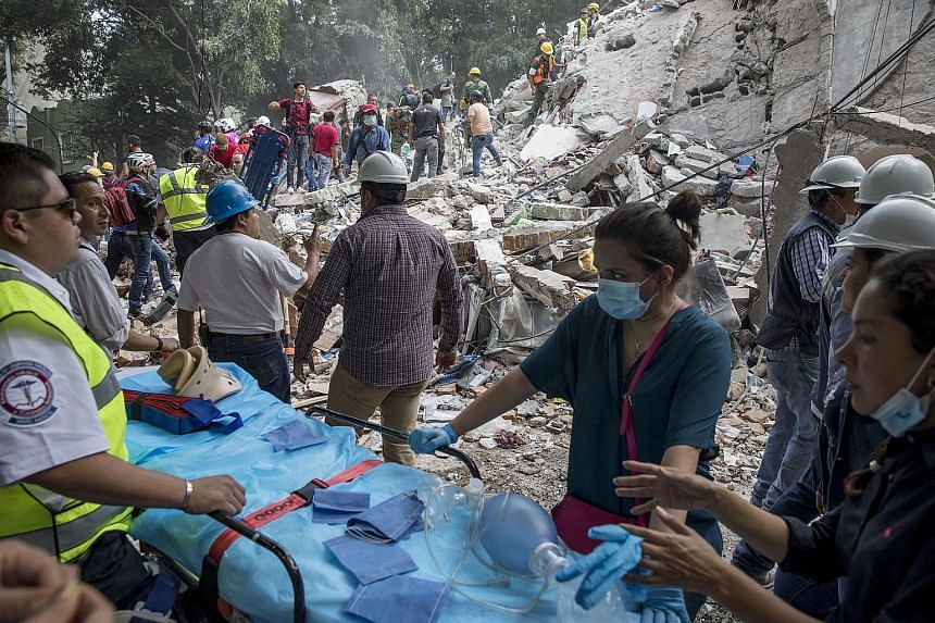 Rescue efforts at a flattened building in Mexico City on Tuesday after the powerful quake caused dozens of buildings to topple, tore gas mains and set off fires across the city and other towns. A collapsed building in the Condesa neighbourhood in Mex
