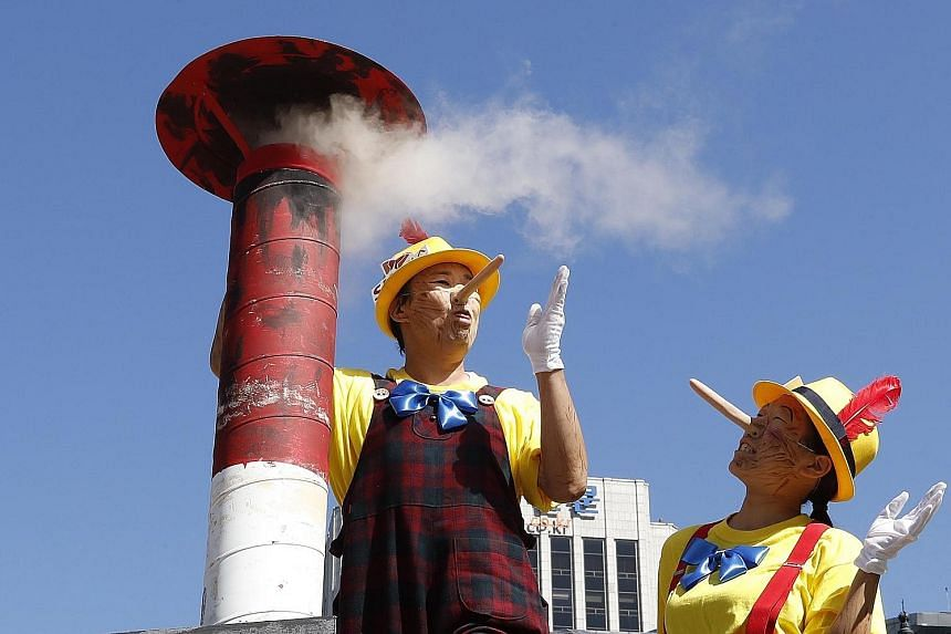 Members of the international environmental group Greenpeace mimicking the fictional character Pinocchio to accuse coal-fired power plant operators of lying that they are eco-friendly, at a protest performance in Seoul, South Korea, yesterday.