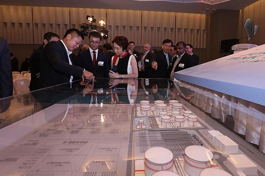Jurong Port CEO Ooi Boon Hoe (far left) and Jurong Port Tank Terminals' (JPTT) general manager Loh Wei discussing the layout of the JPTT with Ms Low Yen Ling. Construction started in May this year and will be completed by 2019. Ms Low said the JPTT w