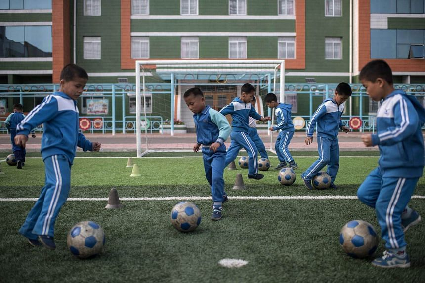 Children playing football at a school for orphans on the outskirts of Pyongyang on April 13, 2017.