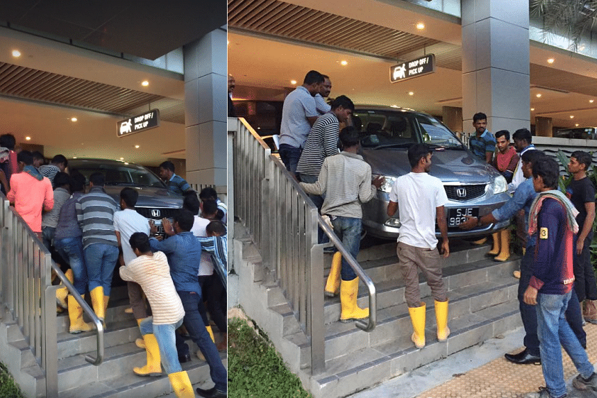 Three foreign workers called their friends to come and help, and the group helped push a car back on the pavement.