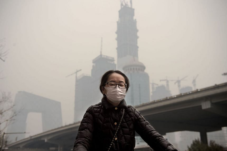 A woman wearing a protective pollutionmask rides a bicycle in Beijing on Mar 20, 2017.