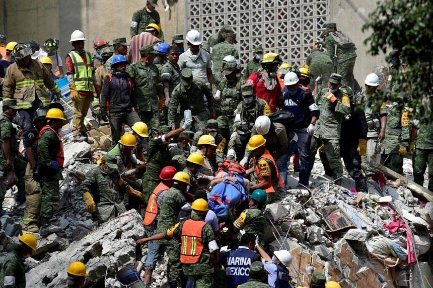 A man is pulled out of the rubble alive in Mexico City on Sept 20, 2017 as the search for survivors continues a day after a strong quake hit central Mexico.