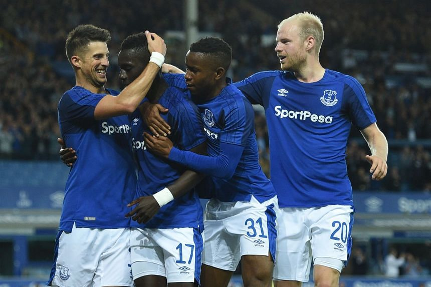 Everton's Senegalese midfielder Idrissa Gueye (second left) celebrates with team mates after scoring a goal.