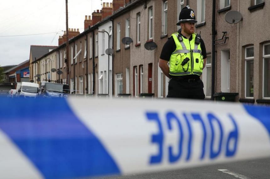 A police officer stands guard at a police cordon near to a house in Newport.