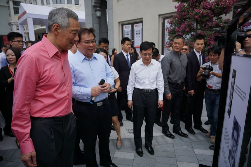 PM Lee Hsien Loong and Mr Samuel Tsien, group chief executive officer of OCBC Bank, viewing historical exhibits on the founding of OCBC in Singapore and China. With them is Finance Minister Heng Swee Keat (in white).
