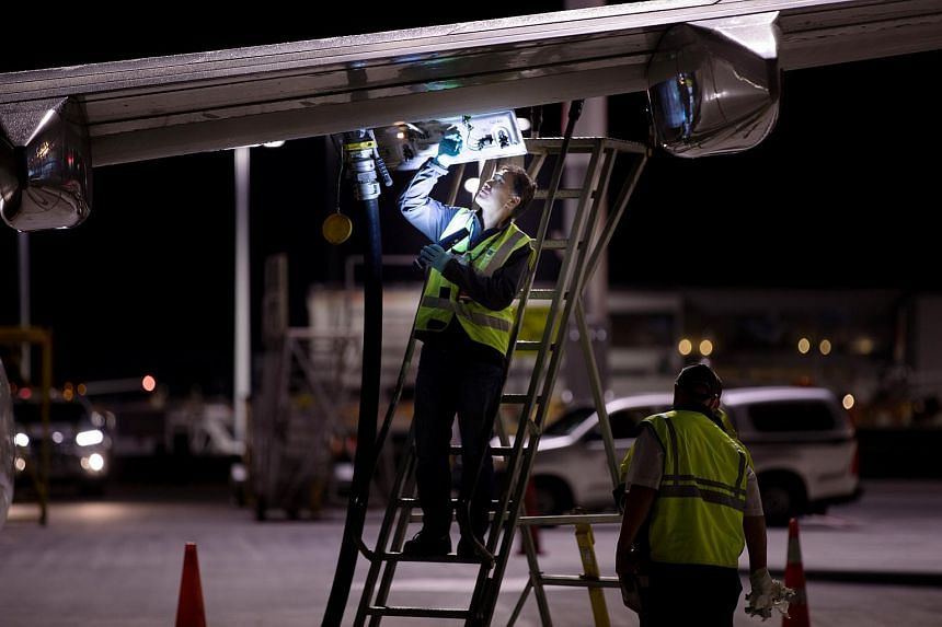 Jet fuel is siphoned directly between two Qantas aircraft on the tarmac of Auckland Airport in New Zealand, on Sept 21, 2017, during fuel shortages which have affected New Zealand's aviation sector.