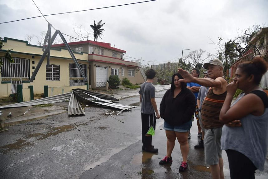 Inhabitants of Puerto Nuevo neighbourhood stand next to roof blown off during the passage of Hurricane Maria, in San Juan, Puerto Rico, on Sept 20, 2017.