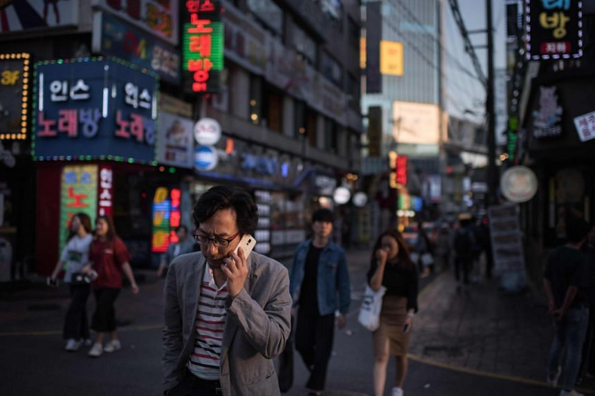 A man holds a mobile phone as he walks along a street in the Sinchon area of Seoul on Sept 13, 2017.
