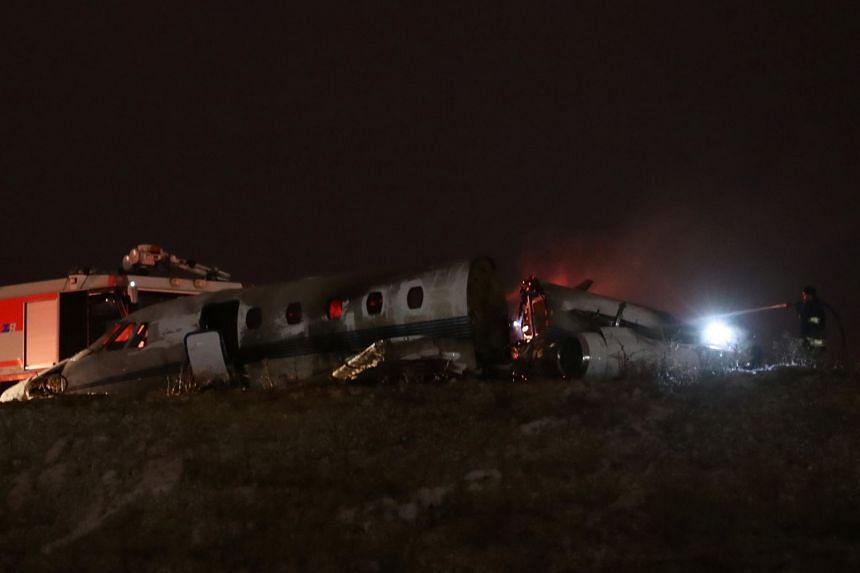 Firefigters stand next to the wreckage of a private jet after it crashed at Ataturk airport.