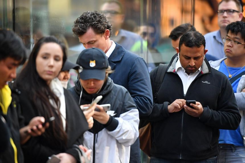 Customers wait in line for new products at the Apple Store in Sydney.