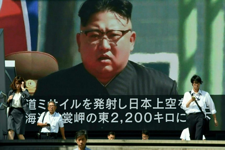 Pedestrians walk in front of a large video screen in Tokyo broadcasting a news report showing North Korean leader Kim Jong Un, following a North Korean missile test that passed over Japan, on Sept 15, 2017.