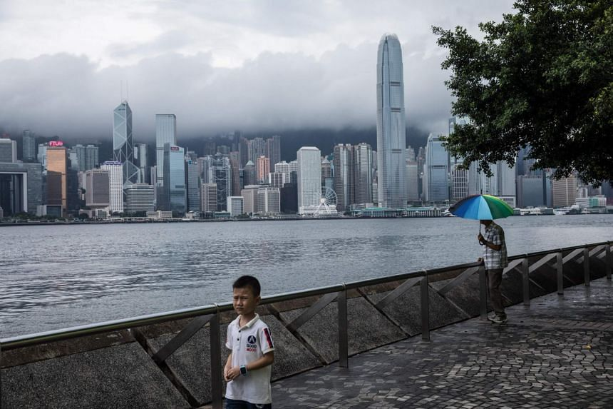 People walk along a promenade before the city skyline in Hong Kong.