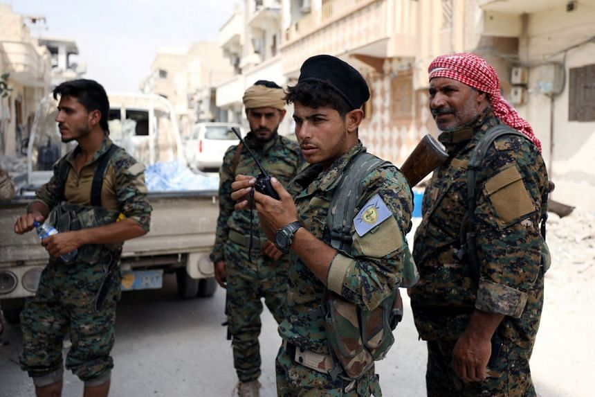 A fighter from Syrian Democratic Forces holds a walkie-talkie in Raqqa, Sept 16, 2017.