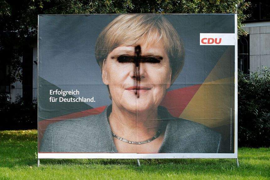 A defaced election campaign poster featuring Merkel in Cologne, Sept 21, 2017.