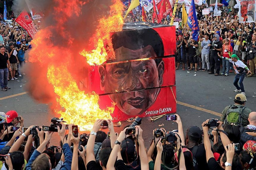 """Protesters burning a cube effigy displaying the face of Philippine President Rodrigo Duterte during a """"National Day of Protest"""" outside the presidential palace in Metro Manila yesterday."""