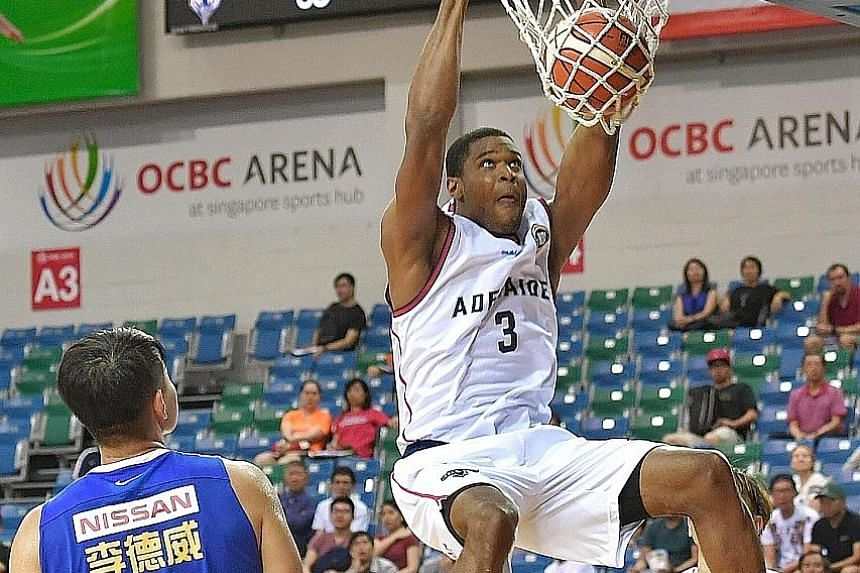 Adelaide 36ers forward Ronald Roberts executing a two-handed slam dunk at the Merlion Cup basketball tournament at the OCBC Arena yesterday, as Yulon Luxgen Dinos' captain Lee Te-wei watches on. The American import scored 19 points as the Sixers thra