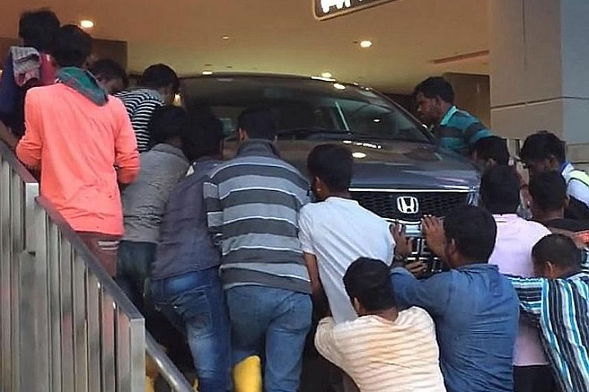 A group of foreign workers pushing a car back to level ground after it ended on a flight of stairs at the Waterway Point mall in Punggol yesterday. Facebook user Garett Lim, 38, who posted a video of the incident, told The Straits Times that the car