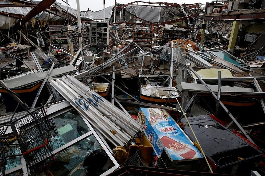 A supermarket wrecked by Hurricane Maria as it ploughed through Guayama city in Puerto Rico on Wednesday. The storm triggered severe flooding and left the entire island without electricity. Governor Ricardo Rossello said it could take months to compl