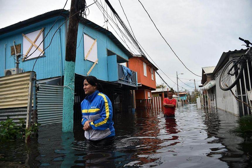 People walk accros a flooded street in Juana Matos, Puerto Rico.