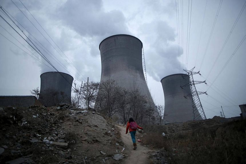 A girl makes her way to her house located next to the cooling towers of a coal-fired power plant in Shijiazhuang, Hebei province, China.