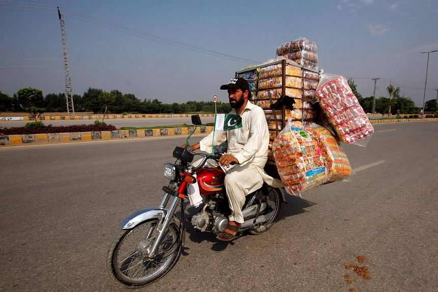 A man rides on bike loaded with packs of potatoes chips while supplying them to shops in Peshawar, Pakistan, on Aug 28, 2017.