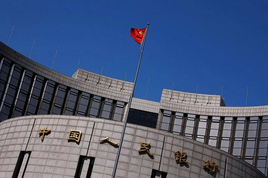 A Chinese national flag flutters outside the headquarters of the People's Bank of China, the Chinese central bank.